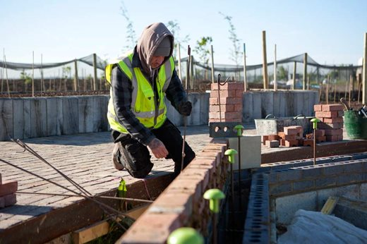 Workman constructing the glasshouse foundations
