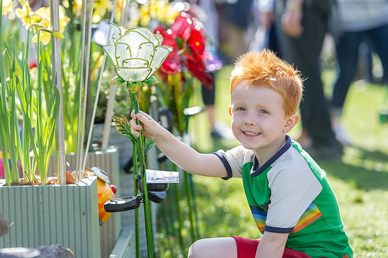 A child looking at flowers on a tradestand